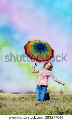 Happy teenage girl with colorful umbrella jumping on field - stock photo