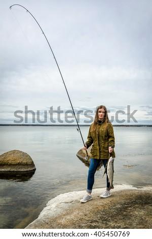 Happy teenage girl with fishing trophy - stock photo