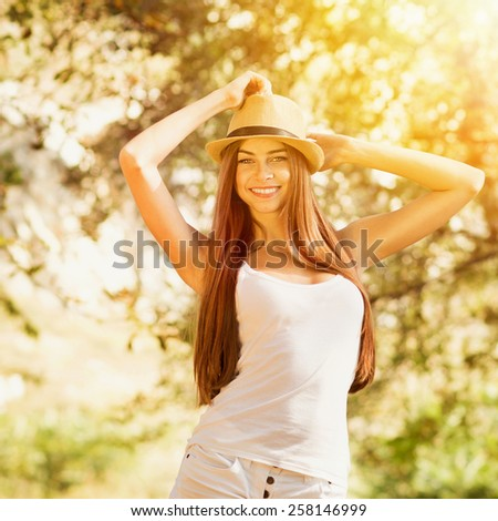 Happy teenage girl with hat in park in summer. Young woman with long hair wearing white tank top and shorts smiling posing. Retouched, filter applied, square format. - stock photo