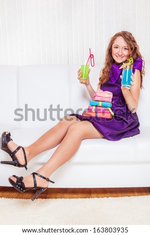 Happy teenage girl with long curly hair, sitting with drinks at the party - stock photo