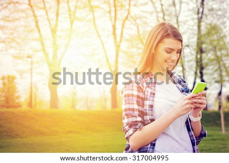 Happy teenage girl with smartphone in park. Beautiful young woman in white and blue plaid shirt texting and smiling outdoors on sunny day. Horizontal, vibrant colors, retouched. - stock photo