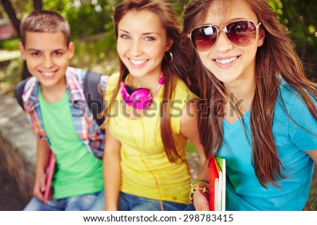 Happy teenage girls and guy looking at camera