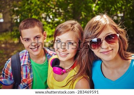 Happy teenage girls and guy looking at camera in natural environment - stock photo