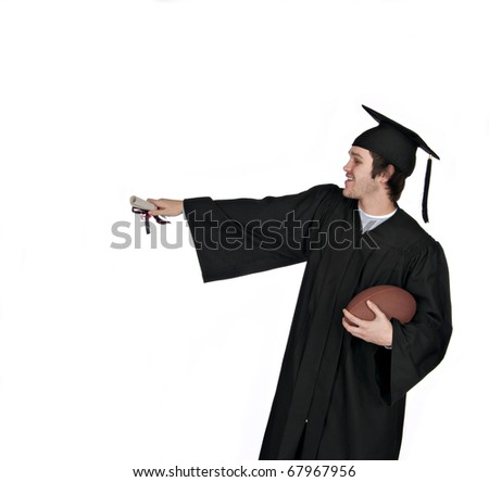happy teenage graduate holding football and holding his diploma out