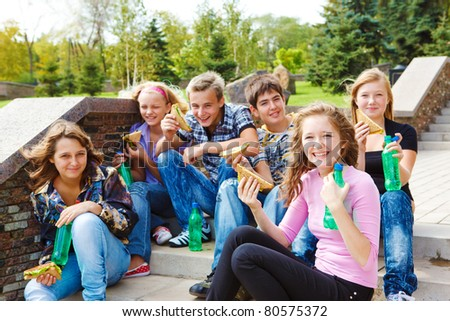 Happy teenage group eating junk food