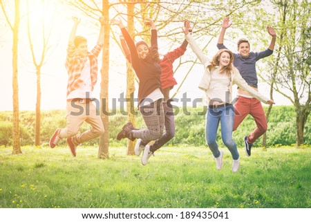 Happy Teenage Group Jumping Outside