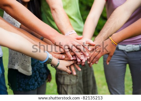 Happy Teenage Group with Hands on Stack - stock photo