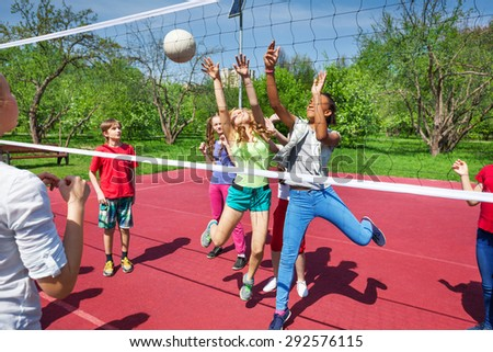 Happy teenage kids play volleyball outside