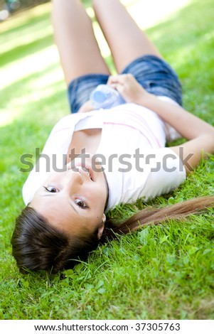 happy teenage lying on grass in park