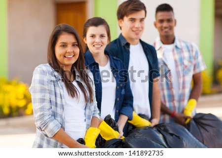 happy teenage volunteers standing with waste bags after cleaning the streets - stock photo