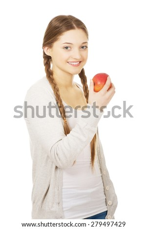 Happy teenage woman holding an apple. - stock photo