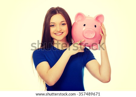 Happy teenage woman holding piggybank.