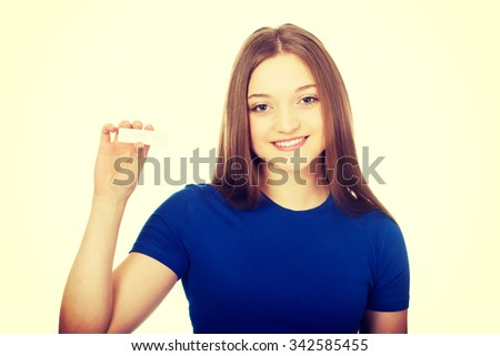 Happy teenage woman holding pregnancy test.