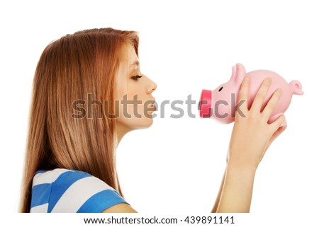 Happy teenage woman kissing a piggybank - stock photo