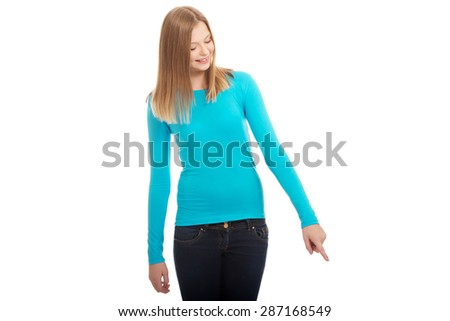 Happy teenage woman pointing down - stock photo