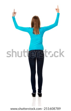 Happy teenage woman pointing up with both hands - stock photo