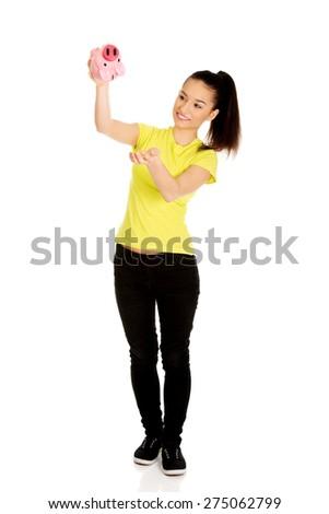 Happy teenage woman shaking piggybank. - stock photo