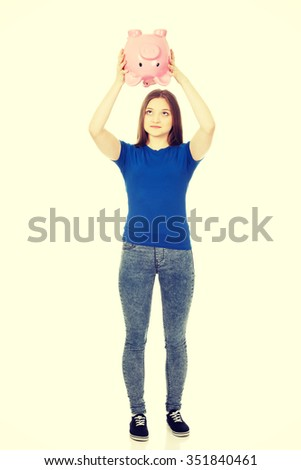 Happy teenage woman shaking piggybank. - stock photo
