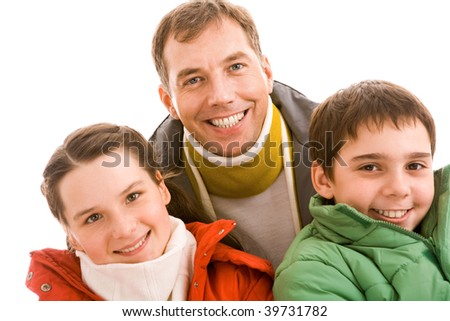 Happy teenaged guy and girl looking at camera with their father behind