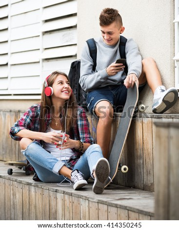 Happy teenager and his smiling girlfriend with they smartphones outdoors  - stock photo