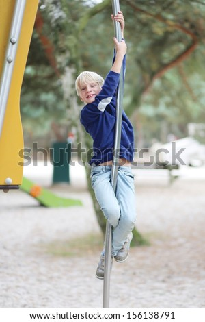 Happy teenager boy having fun on playground in the park after school