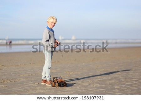 Happy teenager boy plays with remote control car on the beach - stock photo
