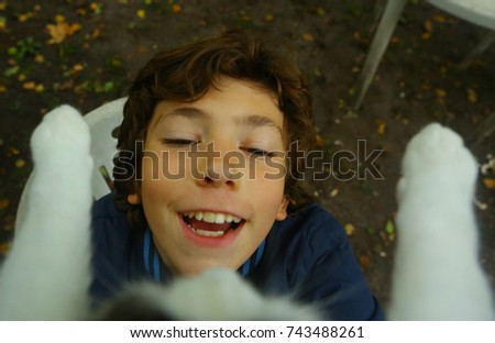 happy teenager boy take cat from the tree close up outdoor summer photo