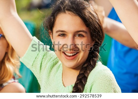 Happy teenager girl cheer for the team during game - stock photo