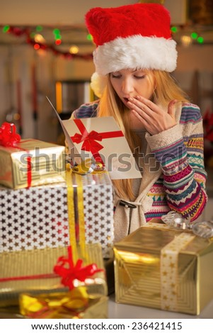 Happy teenager girl in santa hat with stack of christmas present boxes reading christmas postcard - stock photo