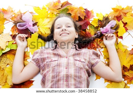 Happy teenager girl lay in maple leafs on white background - stock photo