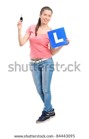 Happy teenager holding a car key and L plate isolated against white background - stock photo