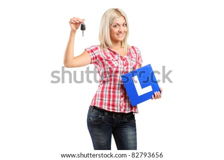 Happy teenager holding a car key and L plate isolated on white background - stock photo