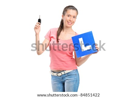 Happy teenager holding a L plate and a car key isolated on white background - stock photo