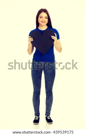 Happy teenager holding paper heart. - stock photo