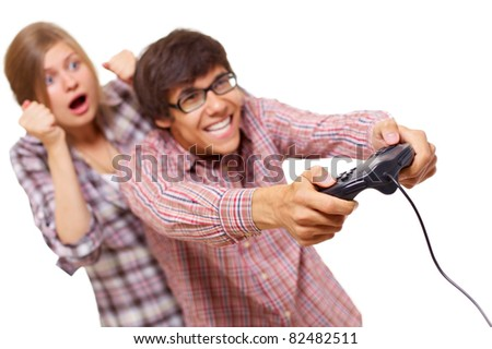 Happy teenager in checked shirt and black glasses playing video game with passion and his girlfriend supports him. Focus on joystick, mask included - stock photo