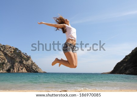 Happy teenager jumping on the beach with the ocean in the background              - stock photo