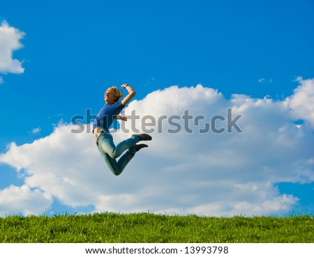Happy teenager jumping over green grass field.