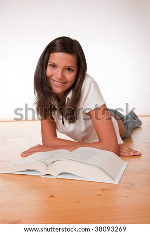 Happy teenager lying down with book on wooden floor