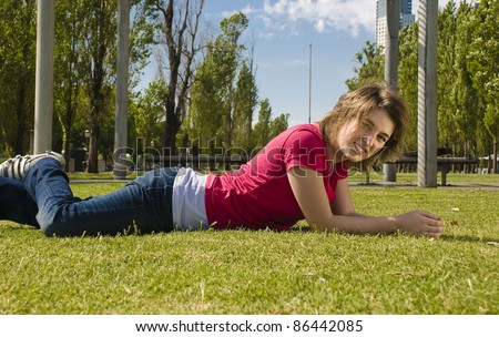 Happy teenager lying on the grass, smiling in the sun. - stock photo