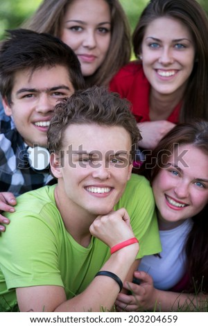 Happy teenager posing with his friends in the park lying