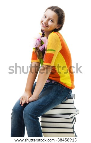 Happy teenager sit on stack of books and smile, isolated on white - stock photo