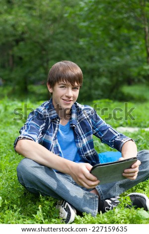 Happy teenager siting on grass in park with tablet, outdoor, schoolboy - stock photo