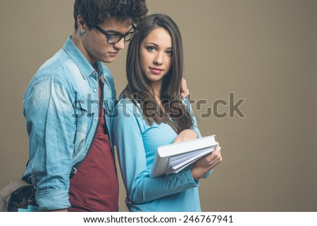 Happy teenager students holding textbooks and smiling - stock photo