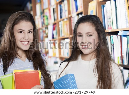 Happy teenager with books in library - stock photo