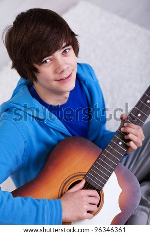 Happy teenager with guitar - closeup