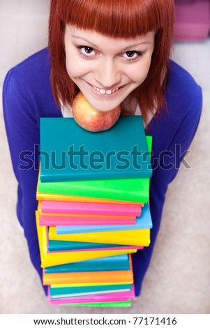 happy teenager with pile of color books, top view