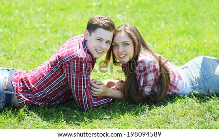 Happy teenagers couple in love lying on the grass in summer sunny day - stock photo