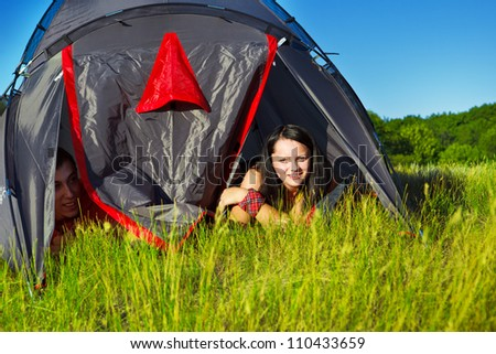 Happy teenagers looking out of the camping tent - stock photo