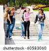 Happy teenagers running, books on stairway - stock photo