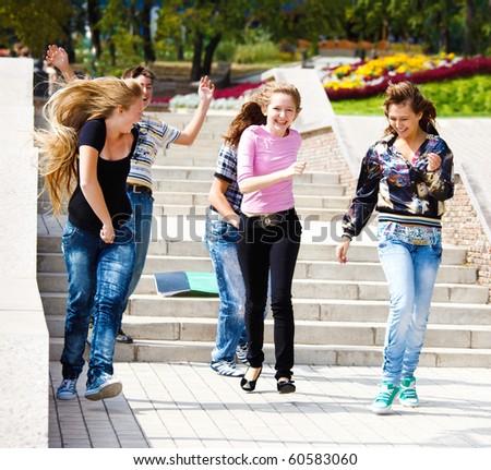 Happy teenagers running, books on stairway - stock photo